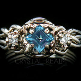 Guinevere four band puzzle ring with step cut blue topaz and two five point round diamonds