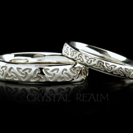 Celtic trinity knot wedding rings in two widths are shown in 14k white gold