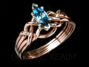 A genuine, marquise blue topaz engagement puzzle ring in 14K rose gold