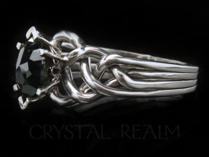 Three-quarter view of a rose cut marquise black diamond puzzle ring