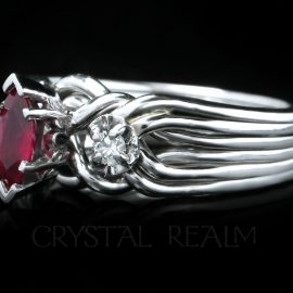 three-quarter view of our six band platinum engagement puzzle ring with marquise ruby center and side diamonds