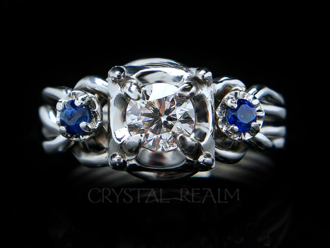 4 piece puzzle ring with round center diamond and two round side sapphires