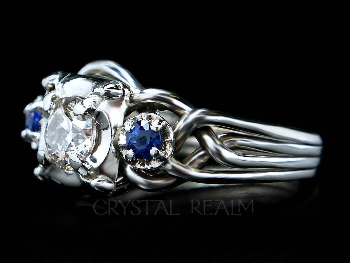 Four band puzzle ring with round center diamond and two blue sapphire accents