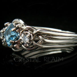 Guinevere puzzle ring in four bands with blue topaz center stone and side diamonds