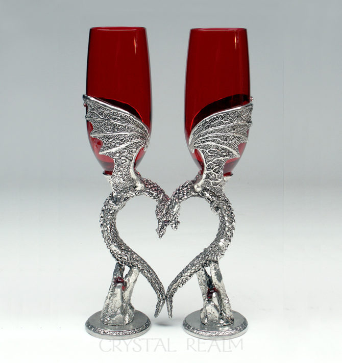 Ruby red toasting glasses held by dragons forming a heart