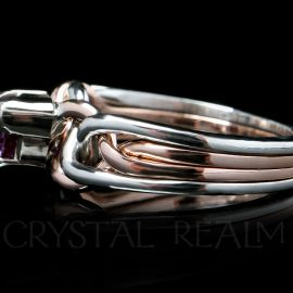 Side view of a triangle-cut, lab-created alexandrite on a platinum and 14K rose gold engagement puzzle ring