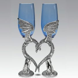 Blue champagne glasses are held by winged dragons in pewter forming a heart when at rest
