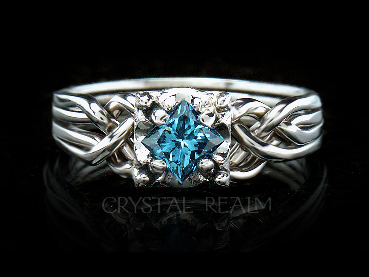 Princess cut blue diamond on Guinevere four band puzzle ring